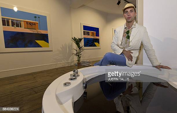 French artist Zevs poses for a photograph alongside his artwork entitled 'Crude Oil' a hot tub filled with oil and paintings entitled 'Oil painting...