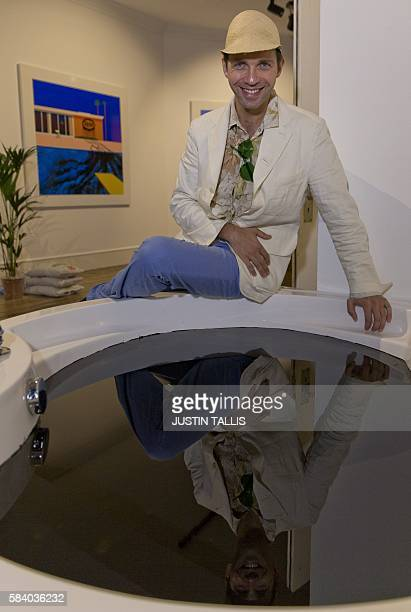 French artist Zevs poses for a photograph alongside his artwork entitled 'Crude Oil' a hot tub filled with oil and in front of a painting entitled...