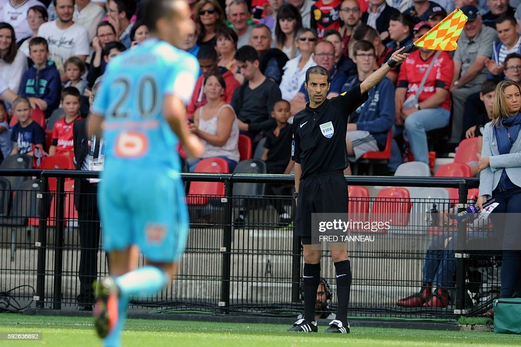French assistant referee Hicham Zakrani waves a flag during the French L1 football match between Guingamp and Marseille on August 21 2016 at the...