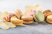 French assorted macarons with orchid flowers on light gray concrete background. Holidays food concept with copy space.