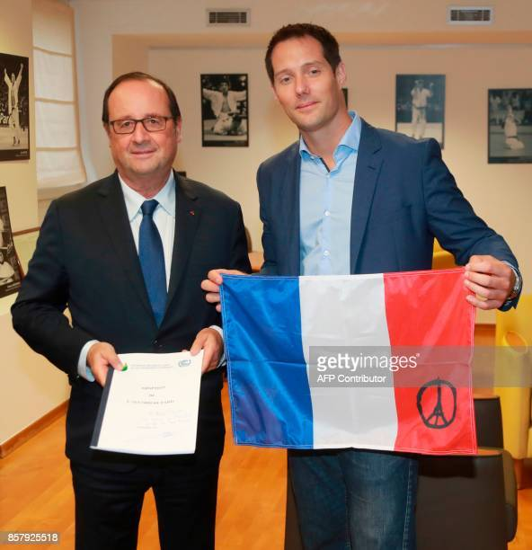 French astronaut Thomas Pesquet and former French President François Hollande pose with a French flag and a copy of the 196nation Paris Agreement on...