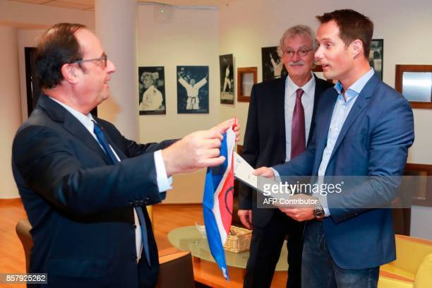 French astronaut Thomas Pesquet hands back to Former French President François Hollande a French flag and a copy of the 196nation Paris Agreement on...