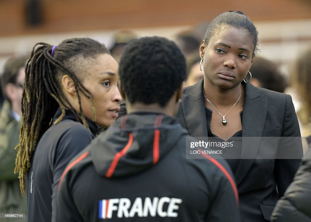 French Athletes Muriel Hurtis (R) and Antoinette Nana Djimou (C) react on March 11, 2015 at the Insep national Sport Institute in Vincennes, outside Paris, during a ceremony in memory of Olympic champion swimmer Camille Muffat, yachtswoman Florence Arthaud and Olympic boxer Alexis Vastine who died two day before with five French TV crew members and two Argentine pilots in the crash of helicopters in Argentina.