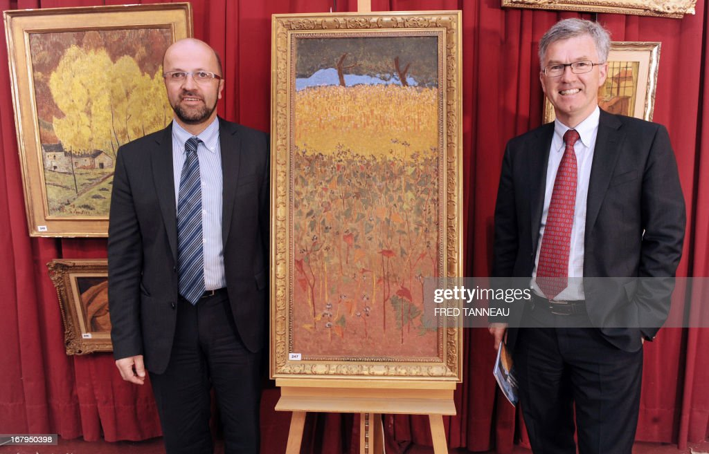 French auctioneers Philippe Lannon (R) and Gilles Grannec pose by the oil on canvas 'Champ de blé d'or et de sarrasin' (Field of gold wheat and buckwheat) made on 1900 by French painter Paul Serusier on May 3, 2013 in Brest, Britany. The painting, which reached a record sell of 1,24 million francs (189.000 euros) for a Serusier in 2001, will go under the hammer once again on May 4.