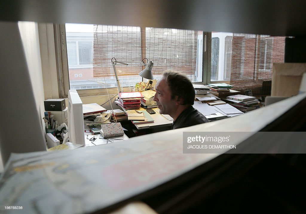French author and illustrator, Emile Bravo poses sitting at his office on November 20, 2012 in Paris. AFP PHOTO JACQUES DEMARTHON