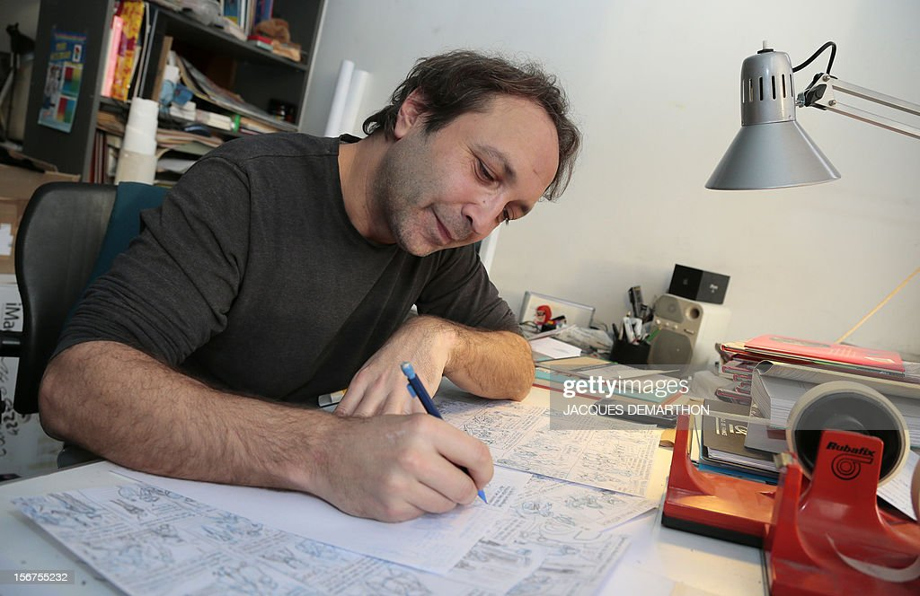 French author and illustrator, Emile Bravo poses working at his office on November 20, 2012 in Paris.