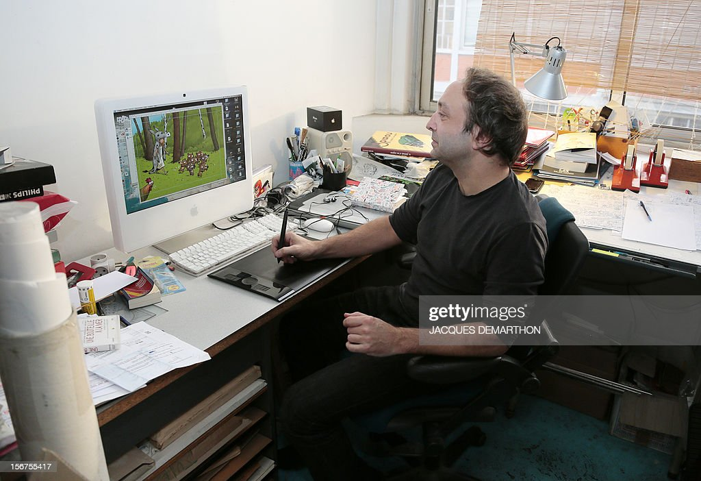 French author and illustrator, Emile Bravo poses working in front of his computer at his office on November 20, 2012 in Paris.