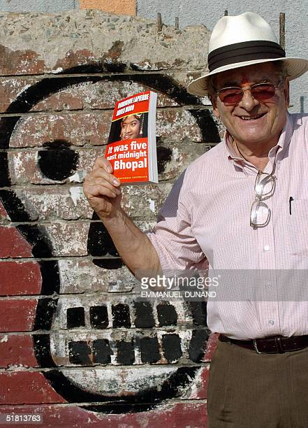 French author Dominique Lapierre poses with a copy of his book talking about the 1984 Bhopal gas leak in front of a skull painted on the enclosing...