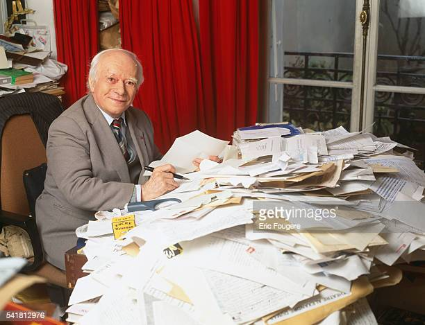 French author Paul Guth reads his mail in his office