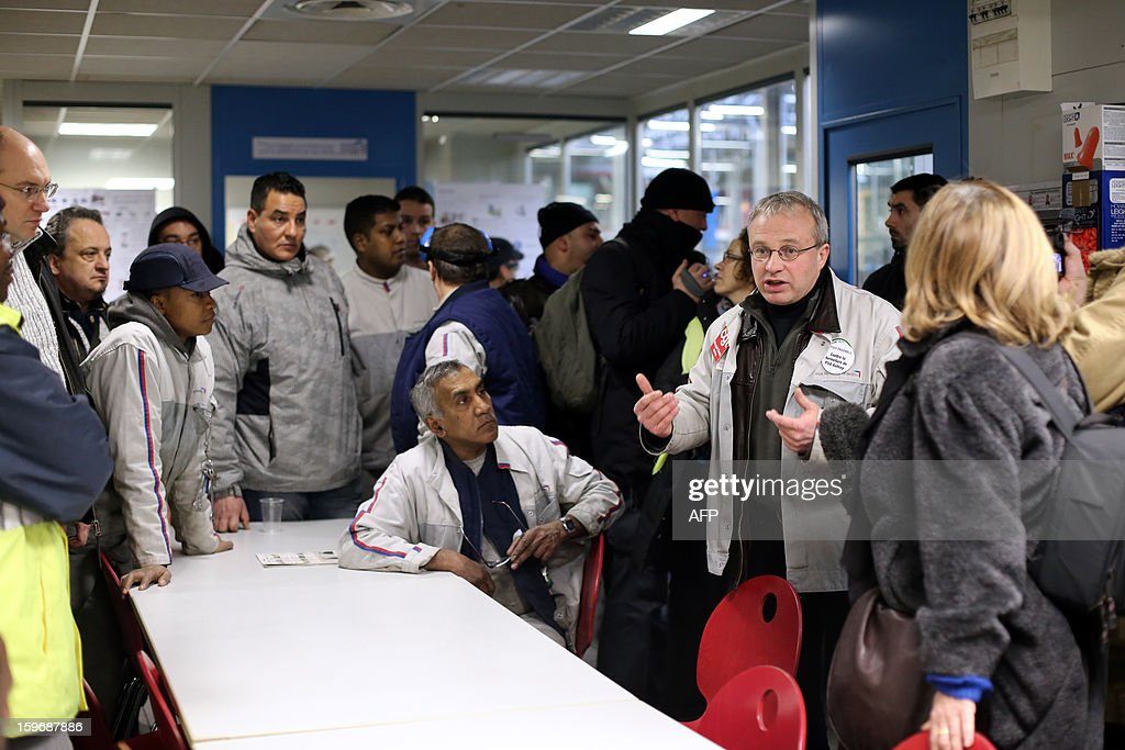 French automobile constructor PSA Peugeot Citroen trade union CGT representative Jean-Pierre Mercier (R) speaks with workers in the PSA factory in Saint-Ouen after workers of the Aulnay's PSA plant entered the plant illegally through a hole in the wall on January 18, 2013, northern Paris. Aulnay's workers are on strike to protest against the closure of their factory. The company was rescued last October with a state guarantee of 7.0 billion euros ($9.0 billion) for its banking and credit arm, and is locked in a restructuring programme involving a plant closure and the loss of 8,000 jobs. SAMSON