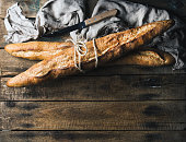 French baguettes on rough rustic wooden background. Top view, copy space