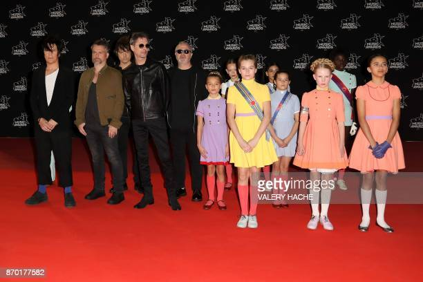 French band Indochine members singer Nicola Sirkis guitarist Oli de Sat and guitarist Boris Jardel pose with girls upon their arrival to attend the...