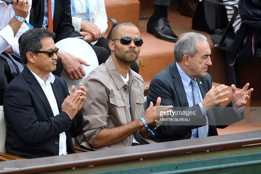 French Basketball player Tony Parker (C) and president of the French Tennis Federation Jean Gachassin attend the men's second round match between France's Jo-Wilfried Tsonga and Cyprus' Marcos Baghdatis at the Roland Garros 2016 French Tennis Open in Paris on May 26, 2016. / AFP / MARTIN