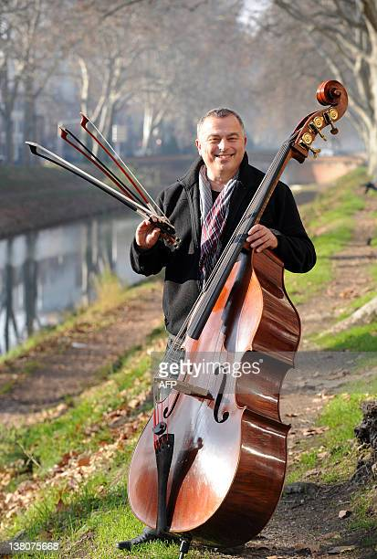 French bassist and director of Toulouse Chamber Orchestra Renaud Gruss poses with double bass bows made of composite materials on January 12 2012 in...