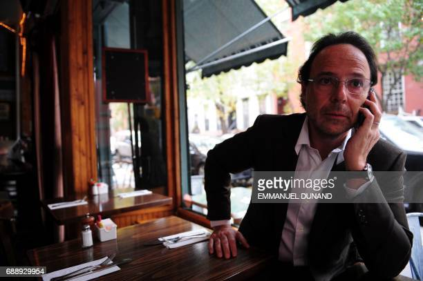 French best selling author Marc Levy makes phone call during a photo session in 'Tartine' a cafe in New York's West Village the neighborhood where he...