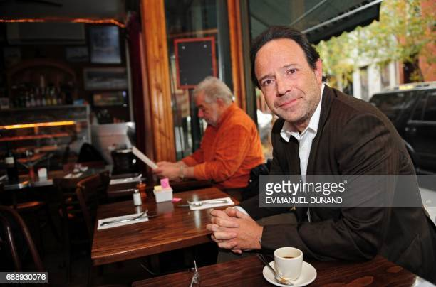 French best selling author Marc Levy makes poses during a photo session in 'Tartine' a cafe in New York's West Village the neighborhood where he...