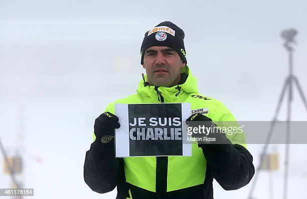 French Biathlon coach Siegfried Mazet holds a placard reading 'Je suis Charlie' in commemoration of the victims of an attack by armed gunmen on the...