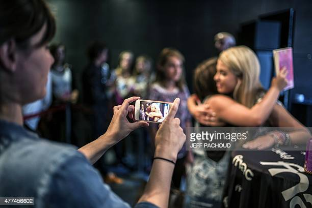 French blogger Marie Lopez aka EnjoyPhoenix gives a hug to a fan as another woman is taking a picture of them during a signing of her first book...