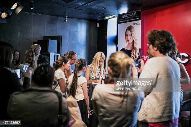 French blogger Marie Lopez aka EnjoyPhoenix is surrounded by fans during a signing of her first book 'Enjoy Marie' on June 17 2015 in a cultural...