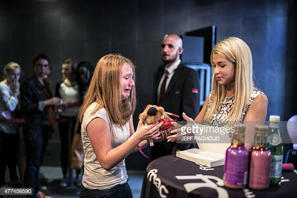 French blogger Marie Lopez aka EnjoyPhoenix receives a soft toy as a gift from a crying fan during a signing of her first book 'Enjoy Marie' on June...