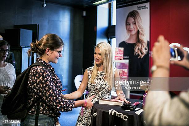 French blogger Marie Lopez aka EnjoyPhoenix speaks to a woman during a signing of her first book 'Enjoy Marie' on June 17 2015 in a cultural store in...