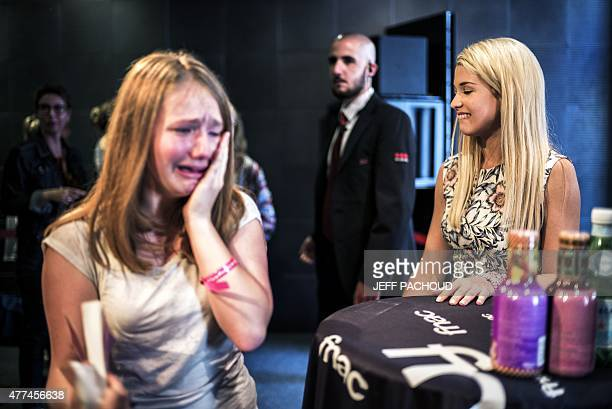 French blogger Marie Lopez aka EnjoyPhoenix stands by a crying fan during a signing of her first book 'Enjoy Marie' on June 17 2015 in a cultural...