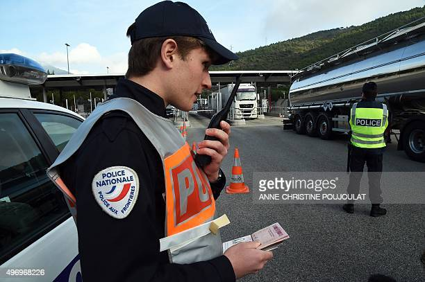 A French border police officer controls passports on the A8 motorway at La Turbie toll near the FrenchItalian border on November 13 2015 30000 police...