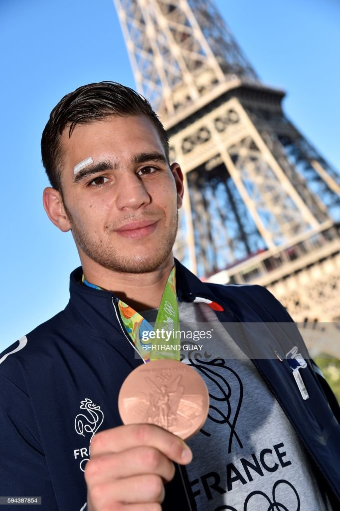 French boxer Mathieu Bauderlique poses with his bronze medal on August 23 in front of the Eiffel tower in Paris France's Olympic team landed in Paris...