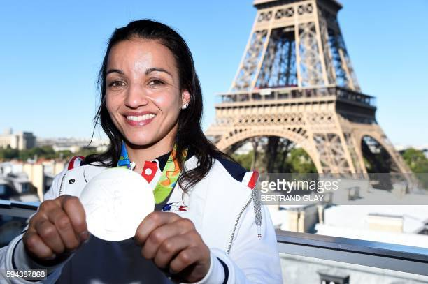 French boxer Sarah Ourahmoune poses with her silver medal on August 23 in front of the Eiffel tower in Paris France's Olympic team landed in Paris on...