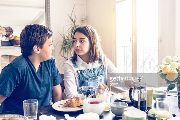 french boy and teenage girl looking eachother at breakfast table