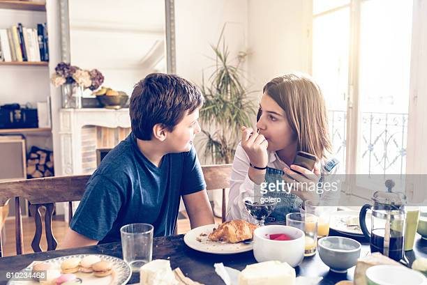 french boy and teenage girl talking at breakfast table