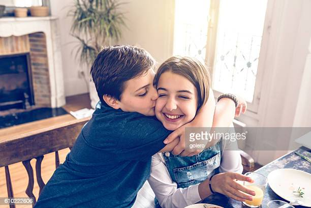 french boy embracing his sister at breakfast table