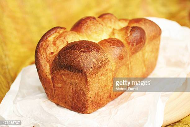 French brioche loaf on paper against yellow backgr