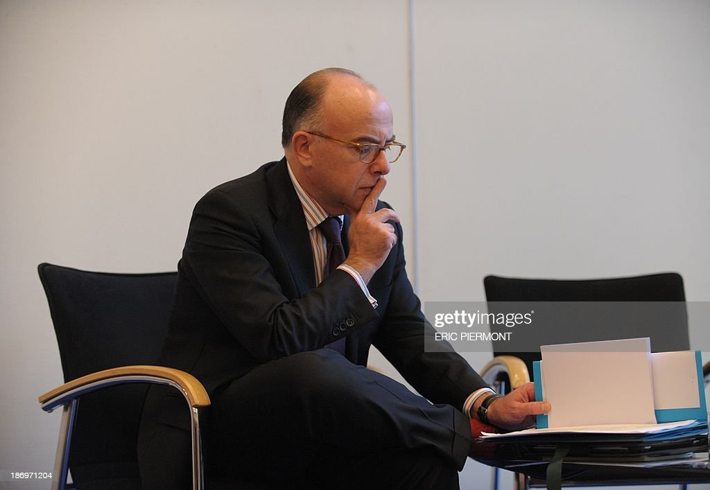 French Budget Minister Bernard Cazeneuve consults a file during a press conference on November 5, 2013 at the economy Ministry in Paris. France will miss its agreed target to cut its public deficit to the EU's 3.0-percent threshold, the European Commission said on Tuesday, putting the 2015 shortfall at 3.7 percent. The French government deficit will hit 4.1 percent this year, according to EU figures, and will fall to 3.8 percent only next year.