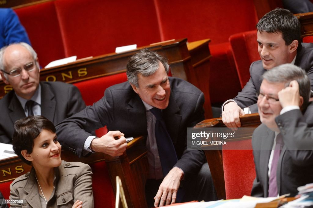 French Budget minister Jerome Cahuzac (C) shares a laugh with Interior minister Manuel Valls (2ndR) during a session of questions to the government, on February 20, 2013 at the National Assembly in Paris. At left, French Minister for Women's Rights and Government Spokesperson Najat Vallaud-Belkacem. AFP PHOTO MIGUEL MEDINA