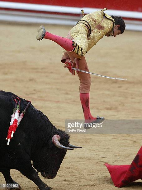 French bullfighter 'matador' Sebastian Castella is tossed by a Nunez de Cuvillo bull 09 July 2004 during the 3rd 'corrida' of the San Fermin fair...