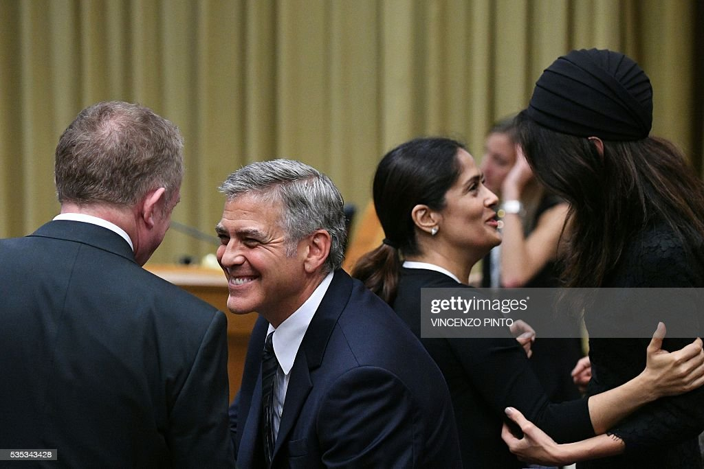 French businessman Francois-Henri Pinault (L) greets US actor George Clooney as his wife actress Salma Hayek greets Amal Clooney (R) before the arrival of Pope Francis for a meeting with the participants of the Sixth World Congress of Pontifical Foundation Scholas, on May 29, 2016 in Vatican. Scholas is an international organization of pontifical right approved and created by Pope Francis in Vatican City August 13, 2013. It combines technology with art and sport to promote social integration and culture of encounter for peace. / AFP / VINCENZO
