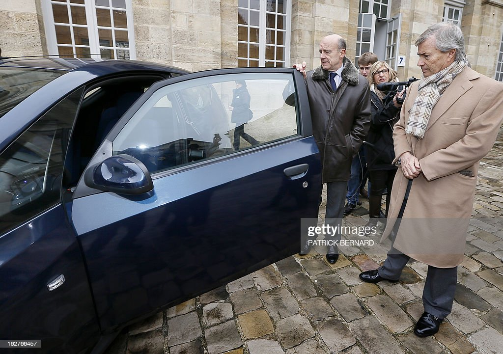 French businessman Vincent Bollore (R) and Bordeaux's Mayor Alain Juppe look on February 26, 2013 at the Bollore electric Bluecar at the Bordeaux Town Hall as part of the car's presentation. AFP PHOTO / PHOTO PATRICK BERNARD