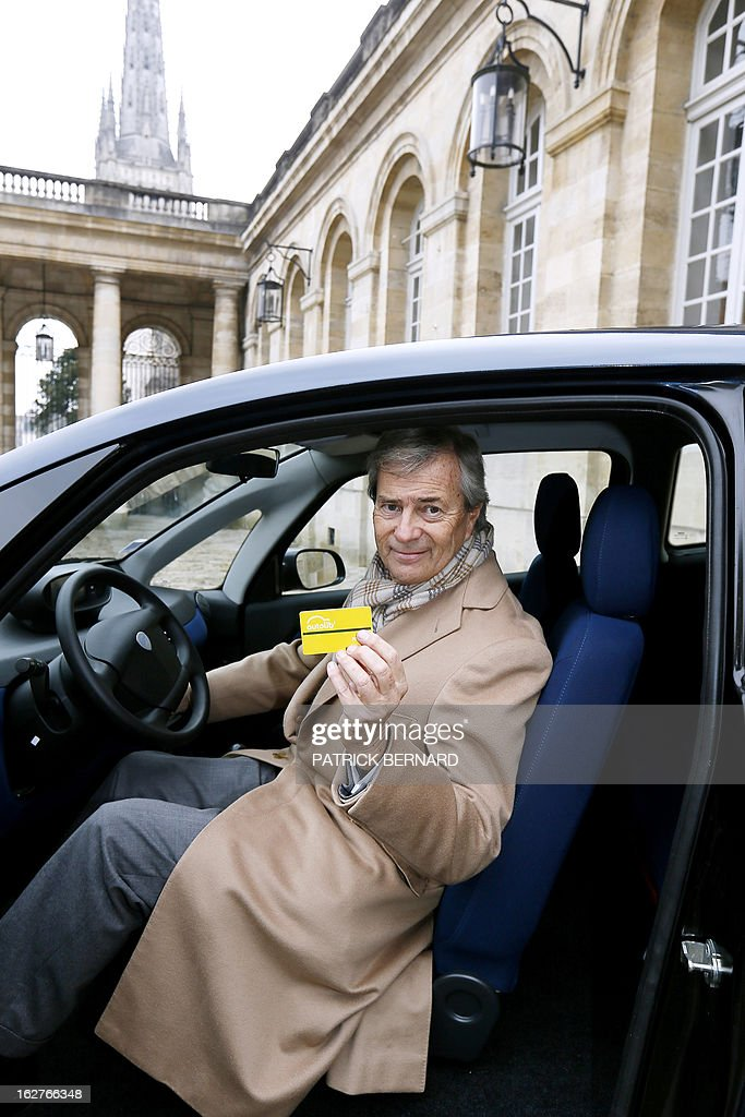 French businessman Vincent Bollore holds on February 26, 2013 his Bluecar card while posing inside his electric Bluecar at the Bordeaux Town Hall as part of the car's presentation to the city's Mayor Alain Juppe.