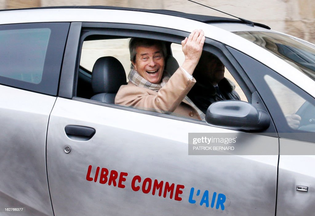 French businessman Vincent Bollore smiles on February 26, 2013 while Alain Juppe (R), Mayor of Bordeaux, drives the electric Bluecar during its presentation at the Bordeaux Town Hall. AFP PHOTO / PHOTO PATRICK BERNARD