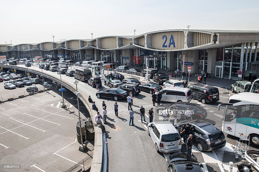 French cab drivers block the road outside Charles de Gaulle airport during a protest against Uber Technologies Inc.'s car sharing service in Roissy, France, on Thursday, June 25, 2015. French taxi drivers are on indefinite nationwide strike as they demand a government crackdown on what they say is Uber's use of unlicensed chauffeurs for its UberPop service. Photographer Balint Porneczi/Bloomberg via Getty Images