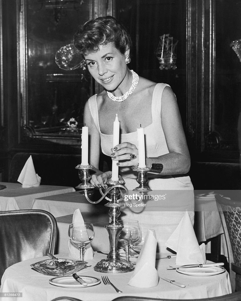 French cabaret singer Helene Cordet (1924 - 1996) supervises the table decorations at her new club in London, 1st November 1957.