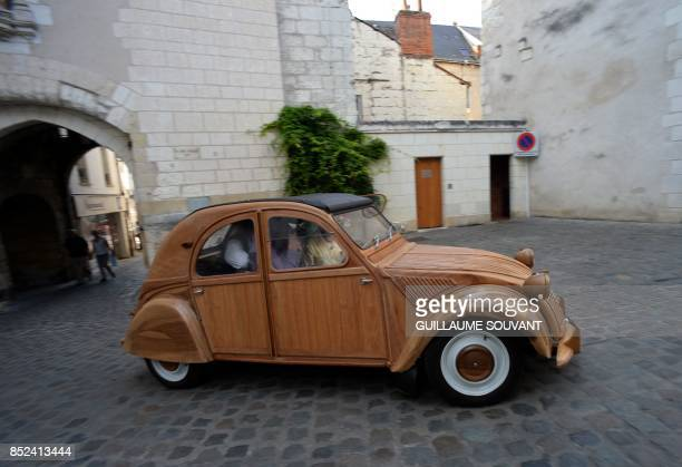 French cabinetmaker Michel Robillard drives his wooden 2CV Citroen car in the streets of Loches Central France on September 23 2017 A retired...