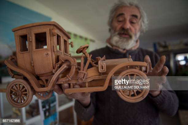 French cabinetmaker Michel Robillard shows his wooden model built at his workshop on March 20 near Loches Central France A retired cabinetmaker has...