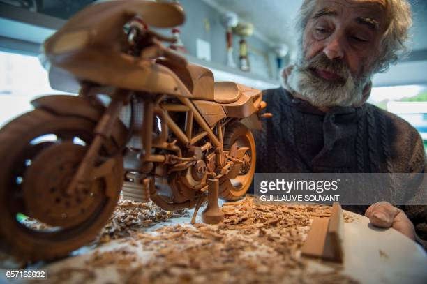 French cabinetmaker Michel Robillard shows one of his wooden model built at his workshop on March 20 near Loches Central France A retired...