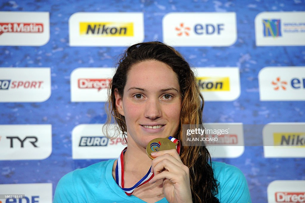 French Camille Muffat poses on the podium after winning the women 100m freestyle final as part of the France swimming championships on Avril 11 in...