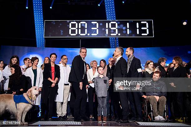 French Canadian singer Garou is flanked by French TV host Nagui and guests as they stand under the board displaying the final number of the evening...
