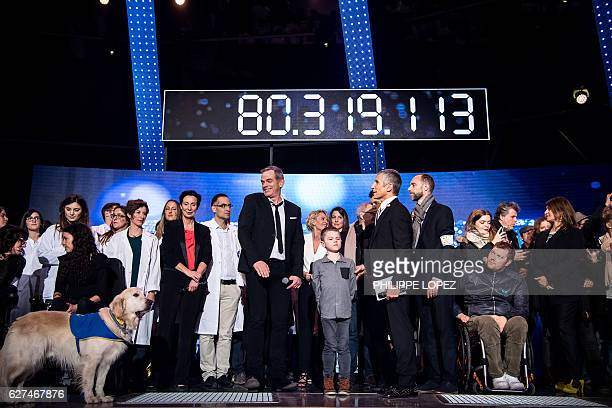 French Canadian singer Garou stands on stage with French TV host Nagui and guests under the board displaying the final number of the evening of the...