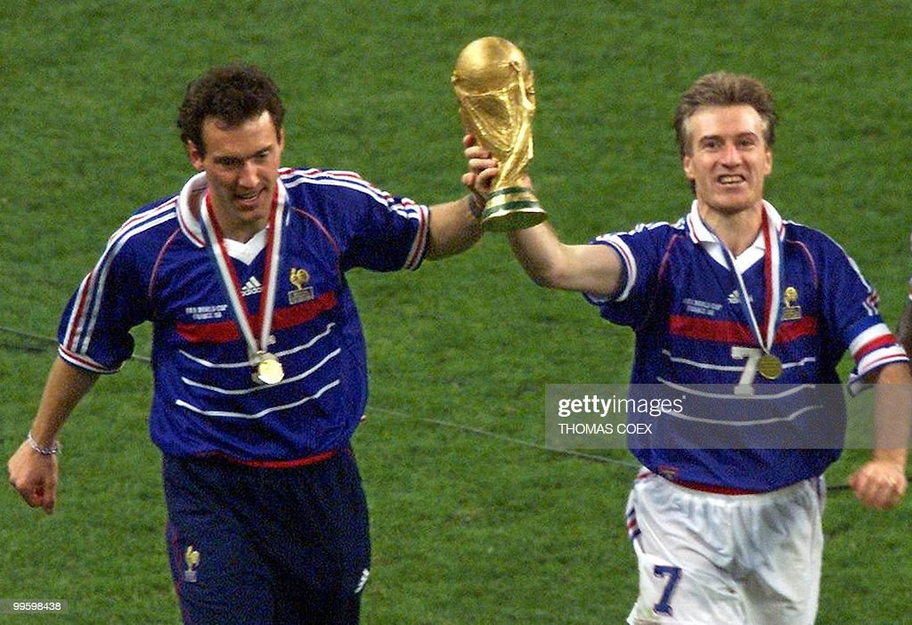 French captain Didier Deschamps (C) and Laurent Blanc (L) hold the FIFA trophy after the 1998 Soccer World Cup final between Brazil and France at Stade de France in Saint-Denis, near to Paris. France won 0-3. (ELECTRONIC IMAGE) AFP PHOTO THOMAS COEX