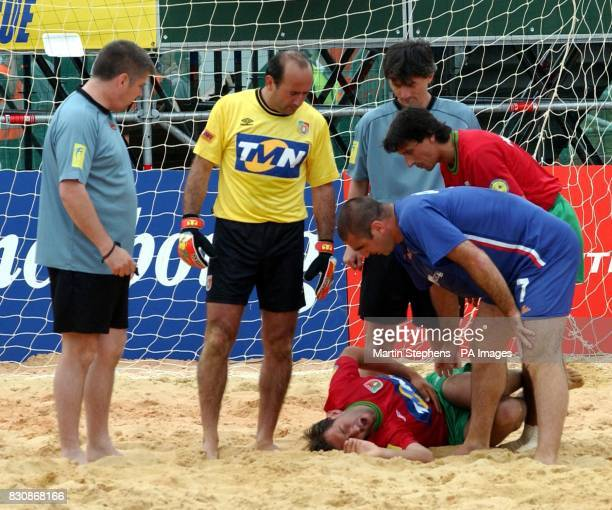 French captain Eric Cantona checks that a member of the Portugal team is alright after clashing with him during the Kronenbourg Cup beach football...